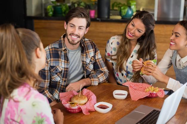 Vrienden met hamburger in restaurant Premium Foto