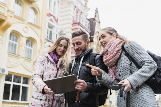 Vrienden met tablet op oude straat Gratis Foto