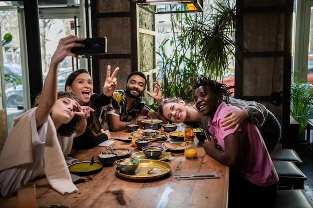 Vrienden nemen foto's van zichzelf in een café tijdens een etentje Premium Foto