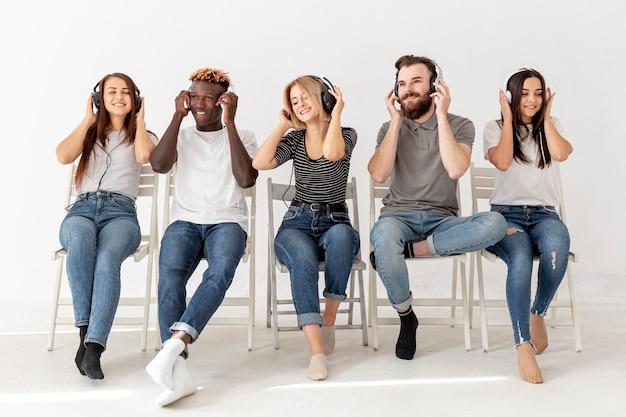 Vrienden op stoelen met koptelefoon luisteren muziek Gratis Foto