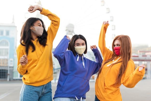 Vrienden poseren op een leuke manier terwijl ze medische maskers dragen Premium Foto