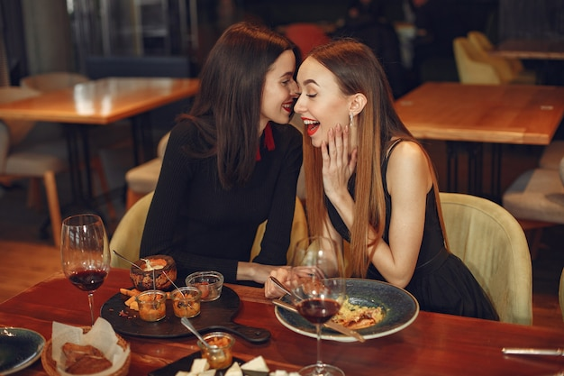 Vrienden praten en plezier hebben op etentje. elegant geklede vrouwen van mensen die aan het dineren zijn. Gratis Foto