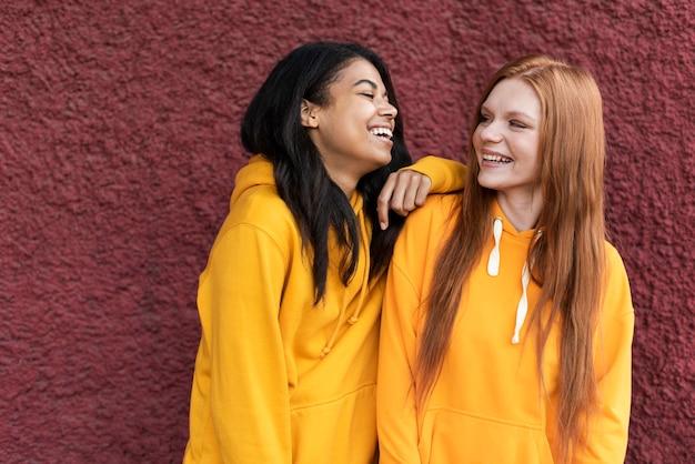 Vrienden praten terwijl ze gele hoodies dragen Gratis Foto