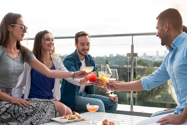 Vrienden roosteren op een feestje Gratis Foto