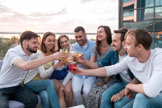 Vrienden roosteren op een terrasfeestje Gratis Foto