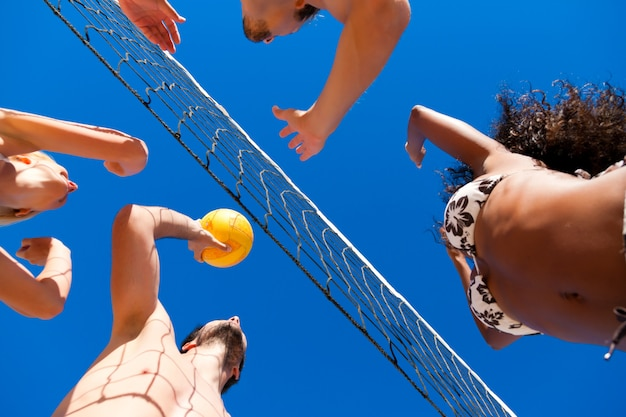 Vrienden spelen beachvolleybal Premium Foto