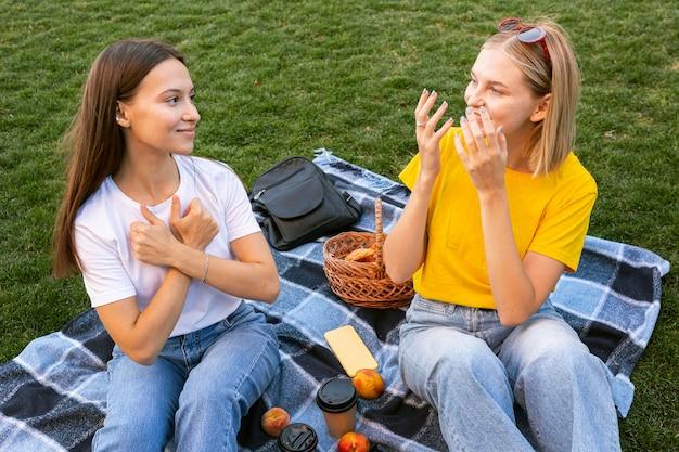 Vrienden van buiten die gebarentaal gebruiken om met elkaar te communiceren Gratis Foto