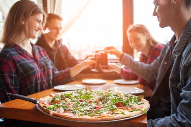 Vrienden van klasgenoten eten pizza in een pizzeria, studenten eten tijdens de lunch fastfood Premium Foto