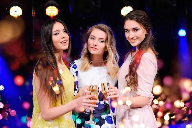 Vrienden vieren het evenement, lachen, dansen en drinken champagne Premium Foto