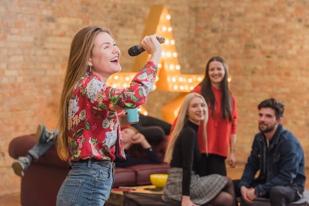 Vrienden zingen karaoke op een feestje Gratis Foto
