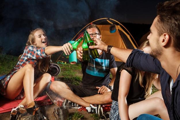 Vrienden zitten in de buurt van vreugdevuur, beer drinken, glimlachen, spreken, rusten Gratis Foto
