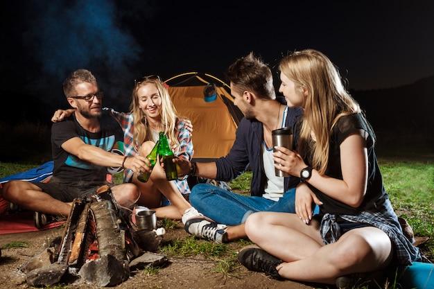 Vrienden zitten in de buurt van vreugdevuur, glimlachen, spreken, rusten, drinken beer Gratis Foto