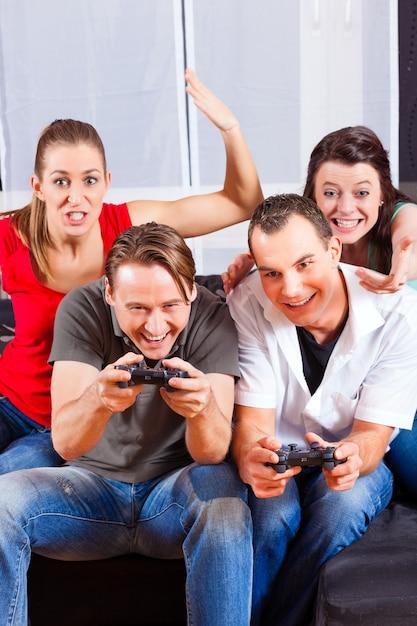 Vrienden zitten voor game console box Premium Foto