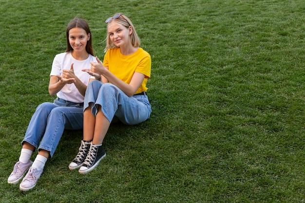 Vriendinnen die gebarentaal buiten gebruiken met kopie ruimte Premium Foto