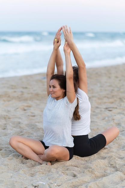 Vriendinnen doen yoga op het strand Gratis Foto