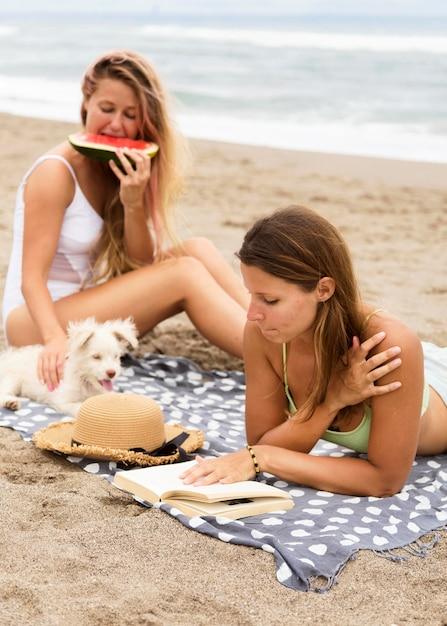 Vriendinnen eten watermeloen op het strand met hond Premium Foto