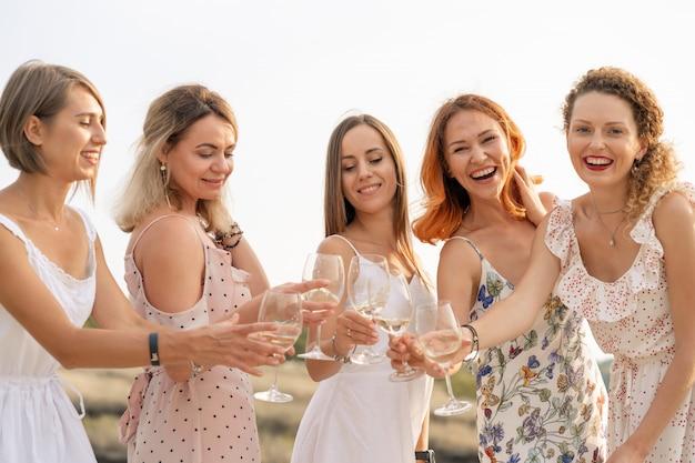 Vriendinnen geniet van een zomerpicknick en hef glazen met wijn Premium Foto