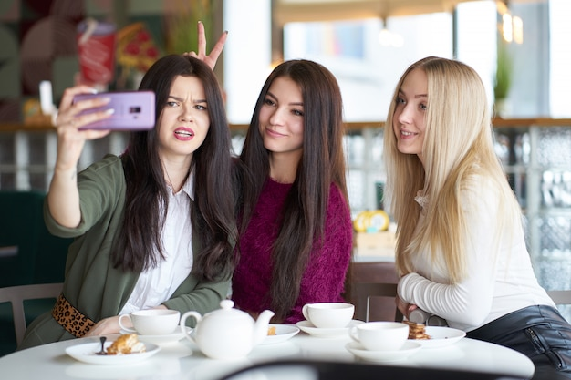 Vriendinnen hebben plezier in café, het drinken van thee en het maken van selfie Premium Foto