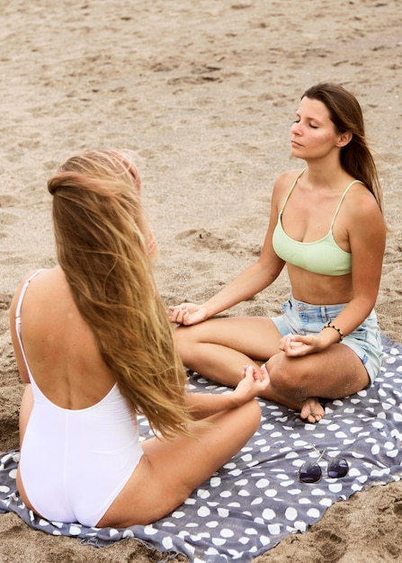 Vriendinnen mediteren op het strand Premium Foto