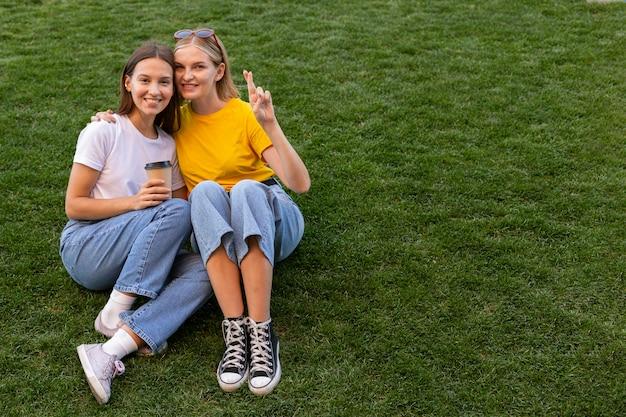 Vriendinnen met behulp van gebarentaal buitenshuis met kopie ruimte Premium Foto