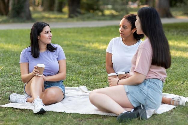 Vriendinnen met koffie samen in het park Gratis Foto
