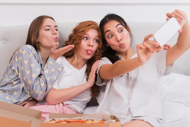 Vriendinnen nemen selfies tijdens pijama party Gratis Foto