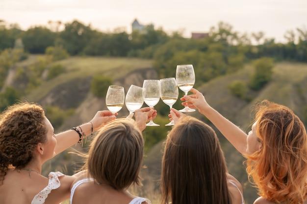 Vriendinnen plezier, proost en drink wijn, en geniet van heuvels landschap picknick. Premium Foto