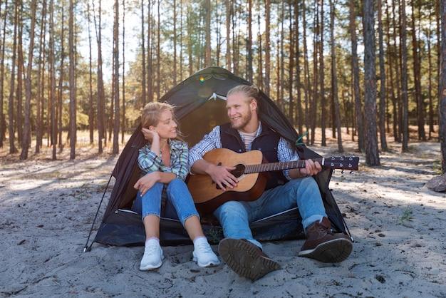 Vriendje akoestische gitaar spelen in de natuur Gratis Foto