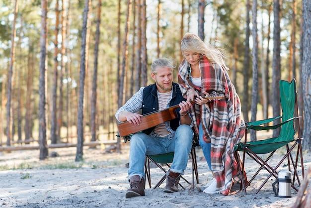 Vriendje akoestische gitaar spelen in het bos Gratis Foto
