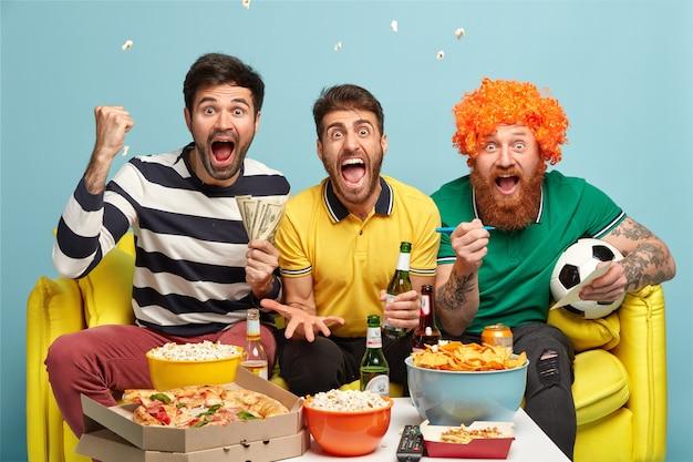Vriendschap, spel, gokken, vrijetijdsconcept. emotionele opgewonden drie mannelijke vrienden kijken naar voetbalwedstrijd op tv thuis, gebalde vuisten, schreeuwen tijdens doel Gratis Foto