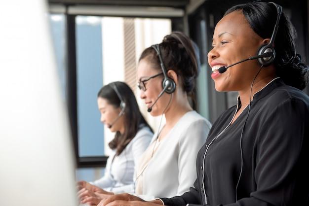 Vriendschappelijke zwarte die microfoonhoofdtelefoon draagt die in call centre werkt Premium Foto