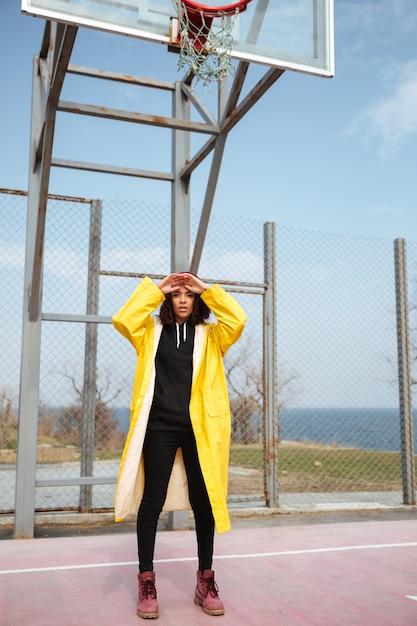 Vrij afrikaanse krullende jonge vrouw die gele laag draagt Gratis Foto