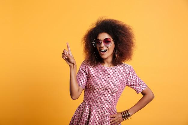 Vrij afro amerikaanse retro vrouw die met afrokapsel met omhoog vinger richt Gratis Foto