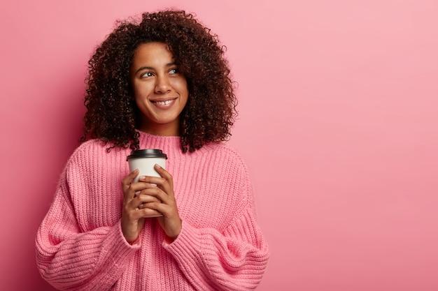 Vrij afro meisje houdt papieren koffiekopje, geniet van vrije tijd, kijkt met een glimlach opzij, draagt een oversized trui Gratis Foto