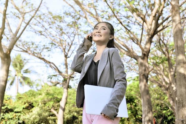 Vrij aziatische onderneemster met telefoon en laptop Premium Foto