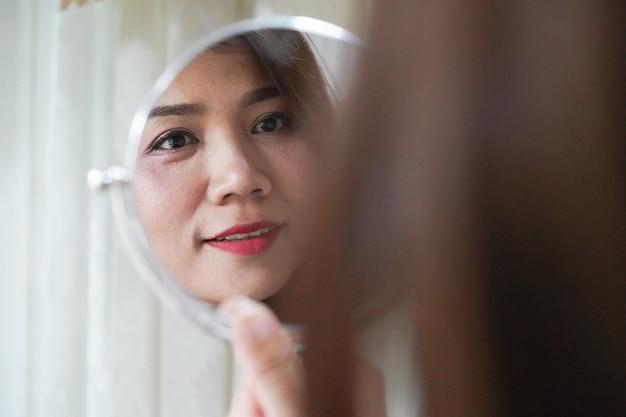 Vrij aziatische vrouw die spiegel voor het controleren van haar rimpel kijkt Premium Foto