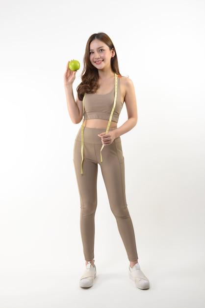 Vrij aziatische vrouw met appel en maatregelenband Premium Foto