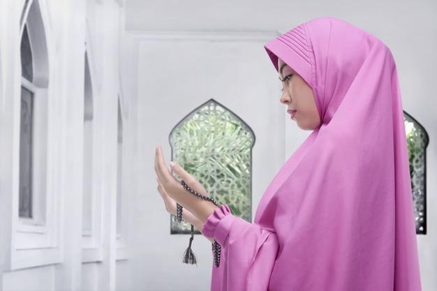 Vrij aziatische vrouwelijke moslim opheffende hand en het bidden Premium Foto