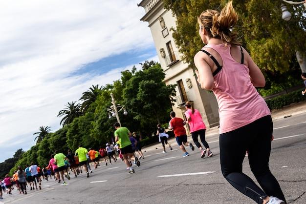 Vrij blond jong meisje die die in een lopende race lopen die door andere agenten wordt omringd. Premium Foto