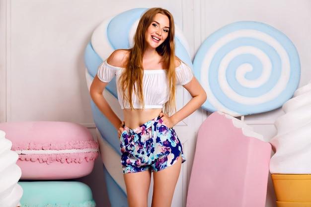 Vrij blond meisje met plezier in de buurt van gigantische zoetheid, lollies, ijs, bitterkoekjes, schattige trendy vrouwelijke outfit, lange haren, pastelkleuren, positieve sfeer. Gratis Foto