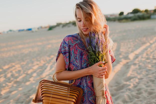 Vrij blonde vrouw die met een boeket van lavendel op het strand loopt. sunset kleuren. Gratis Foto