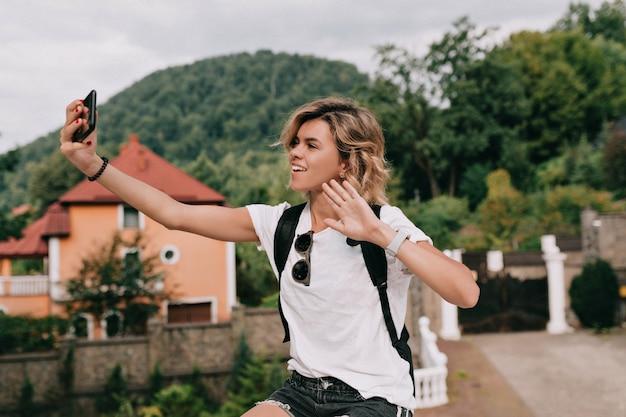 Vrij charmante reiziger vrouw selfie op smartphone maken over berg in zonnige goede dag. reisconcept, vakantie, reis Gratis Foto