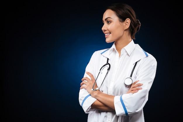 Vrij donkerbruine vrouw opzij en arts die glimlacht kijkt Gratis Foto