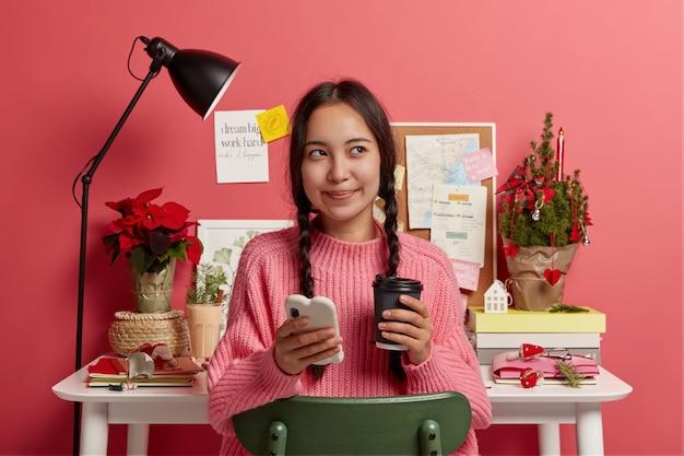 Vrij donkerharige meisje gebruikt smartphone voor surfen op sociale netwerken, drinkt afhaalmaaltijden koffie, kijkt weg, gekleed in gebreide trui, vormt tegen desktop met versierde kerstboom Gratis Foto