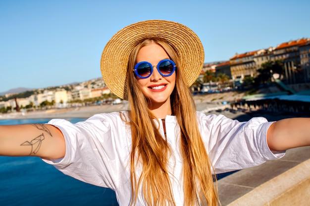 Vrij elegante blonde mooie vrouw selfie vooraan maken op mooi strand Gratis Foto