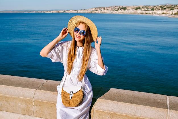 Vrij elegante vrouw, gekleed in witte jurk, strooien hoed en tas poseren in de buurt van de oceaan Gratis Foto