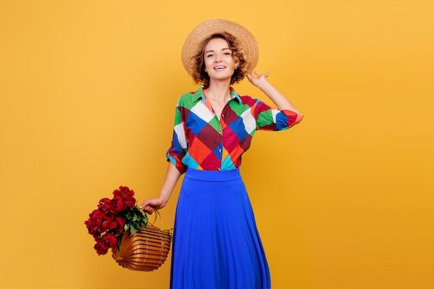 Vrij europese vrouw in blauwe jurk met boeket bloemen op gele achtergrond. stro hoed. zomerstemming. Gratis Foto