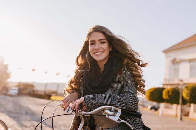 Vrij europese vrouw met prachtig krullend haar poseren in koude herfstdag op stadsplein Gratis Foto