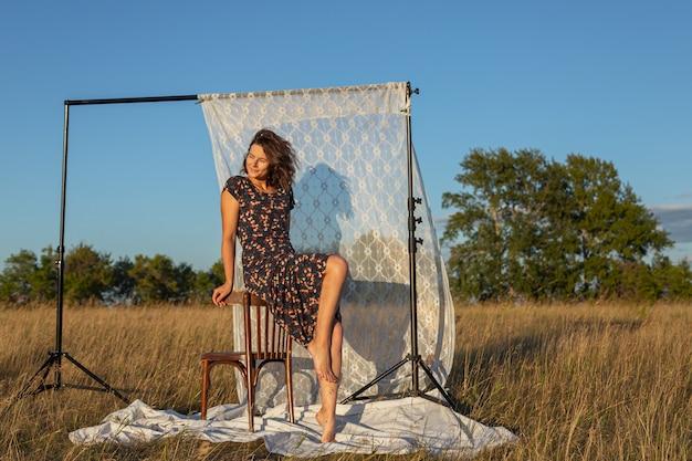 Vrij frisse jonge vrouw zittend op een stoel buiten in het veld en het dragen van in jurk op de achtergrond een rek met witte gordijnen. concept van zomervakantie in dorp en live stijl Premium Foto