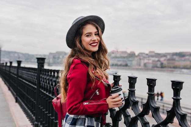 Vrij gekrulde vrouw met lichte make-up genieten van uitzicht op de stad vanaf de brug in herfstdag Gratis Foto